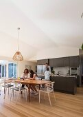 Family in open kitchen with dining table and parquet floor