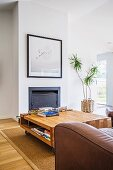 Solid coffee table on castors in front of a fireplace with a framed picture