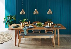 Laid dining table with wooden bench under pendant lights in front of petrol-colored wooden paneling