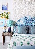 Bedroom in a mix of patterns;Bed with blue upholstered headboard in front of pattern wallpaper and retro bedside table with table lamp