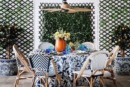Wicker chairs around a laid table with a floral, blue and white tablecloth under a ceiling fan