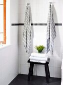 Black wooden stool with stack of towels in front of white tiled wall with hanging towels