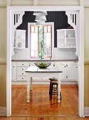 Decorated doorway with white wooden frame and view of traditional kitchen table in country house kitchen