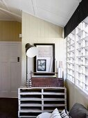 Pallet furniture with tool box and floor lamp in front of wood-clad wall next to louvre window