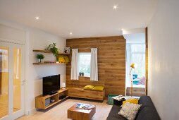 Lounge area with wood-clad wall and matching bench and sideboard next to open doorway