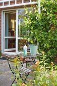 Stuhl und Tisch mit Eimer und Putzmittel auf der Terrasse