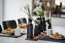 Gedeckter, weisser Ostertisch mit in schwarzem Papier gewickelten Flaschen als Blumenvasen und schwarzen Tischsets
