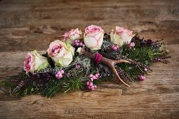 Alpine-style arrangement of roses, antlers, snowberries and heather