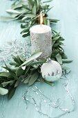 Girlande aus Olivenzweigen mit silberner Kerze, Schneeflocke und Christbaumkugel