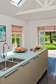 Island counter under exposed roof structure in modern kitchen