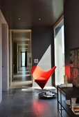 Classic red easy chair next to panoramic window in room painted dark grey