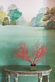 Red-painted branches on console table against mural of green landscape