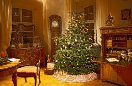 Klassisch geschmückter Weihnachtsbaum im traditionellen Wohnraum mit antiken Möbeln