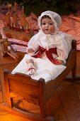 Historisches Weihnachtsspielzeug: Antike Puppe mit Schlafhaube in einem Puppenbettchen