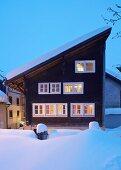 Façade with illuminated windows in wintery twilight atmosphere