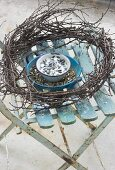 Bird food in enamel bowls and wreath of twigs on garden chair