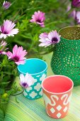 Colourful tealight holders next to purple Cape daisies