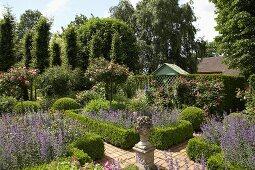 Durch Buchshecken eingefasste Beete und hochstämmige Rosen in Sommergarten