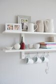 White crockery on a wall shelf with white cups hanging on hooks