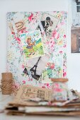Vintage-style clippings from French magazines on floral fabric pinboard