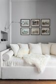 Cushions and sheepskin blanket on white couch below pictures on wall