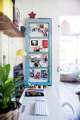 White desk with keyboard and screen, light blue vintage window sash on the side as a pin board for family photos