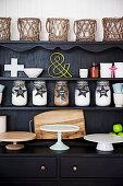 Black sideboard with various cake platters, storage jars and basket lanterns