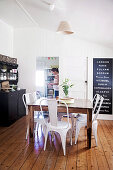 White chair classics around massive wooden table in country dining room