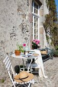 Sunny seating area outside rustic country house with garden bench and lattice window in background