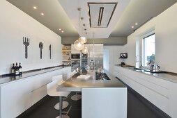 Island counter and long, minimalist base units in modern kitchen