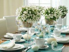 Gedeckter Ostertisch mit weissen Glockenblumen im Stielglas und Windlichter auf Tapete als Tischläufer