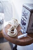 Vintage tin and rope on wooden stool seat