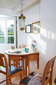 Sunny dining area with drop-leaf table and wooden chairs