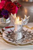 Lit, stags-head candle on plates with gilt patterns
