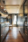 Elegant stainless steel kitchen counter with extractor hood and rustic wooden floor in elegant renovated interior