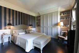 Wallpaper with wide stripes and fitted wardrobes in elegant bedroom