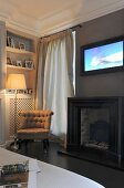 Gas fire, TV and easy chair in corner of living room