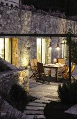Garden furniture on illuminated terrace against stone façade