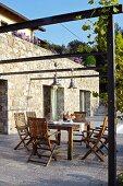 Set table in seating area below pergola on Mediterranean terrace against stone façade