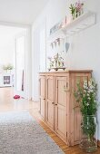 Glass vase of flowers next to half-height wooden cabinet in hallway