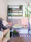 Floral and gingham cushions on bench below bowls and potted plant on rustic wall-mounted shelves