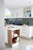 White, glossy modern kitchen with glass splashbacks and island counter