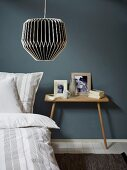 Black and white lantern-style lamp above bed with striped bed linen and bedside table