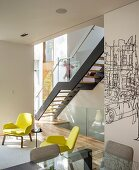 Modern staircase with glass balustrade and two yellow armchairs in contemporary interior