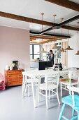 Esszimmer mit weißen Möbeln und Blick in die offene Küche
