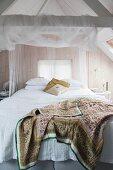 Romantisches Schlafzimmer unter dem Dach mit Bretterwand