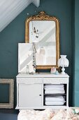 Antique gilt-framed mirror on top of old cabinet
