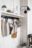Hand-made linen bags hung from black hooks in cloakroom