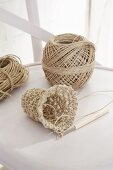 Crochet work, crochet needle and parcel string on white chair
