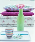 Pale green vase between striped beaker on tray and stacked cushions with vintage floral patterns